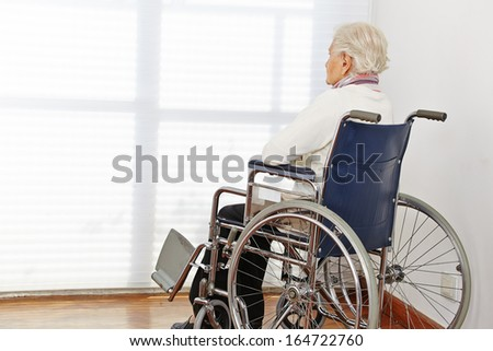 Lonely senior citizen woman in wheelchair in a nursing home - stock photo
