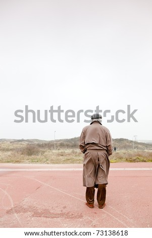 Lonely senior man with raincoat and hat standing on road on cloudy day. - stock photo