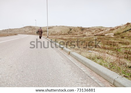 Lonely senior man with raincoat and hat walking on road. Lost. - stock photo