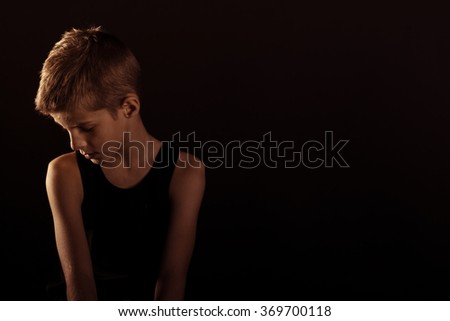 Lonely Slim Boy in Sleeveless Shirt Looking Down Against Dark Background with Copy Space on the Left Side. - stock photo