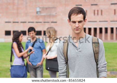 Lonely student posing while his classmates are talking outside a building - stock photo