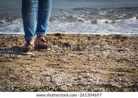 Lonely teen girl walking on the beach