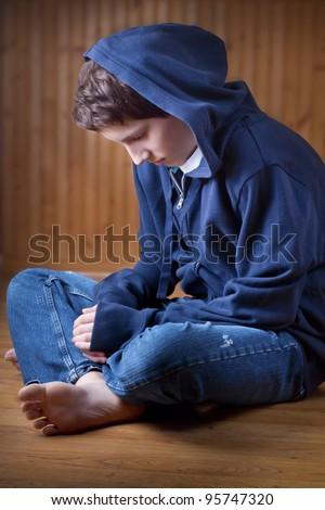 Lonely teenage boy sitting on the floor - stock photo