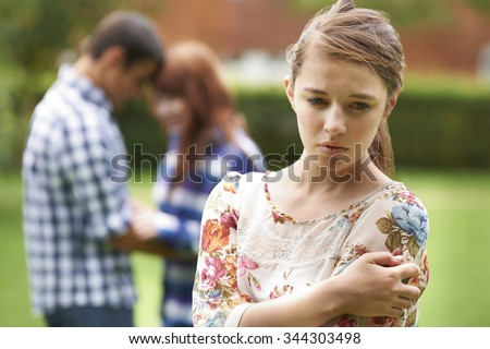 Lonely Teenage Girl Jealous Of Couple In Background - stock photo