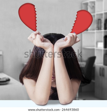 Lonely teenage girl sitting alone in the bedroom while holding broken heart - stock photo