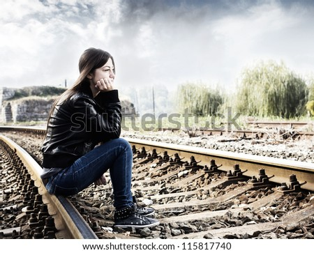 Lonely teenage girl sitting on railroad and thinking. - stock photo