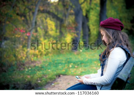lonely teenage girl with cell phone sitting in autumn setting - stock photo