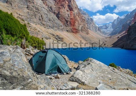 Lonely tent stands on the shore of a beautiful mountain lake - stock photo