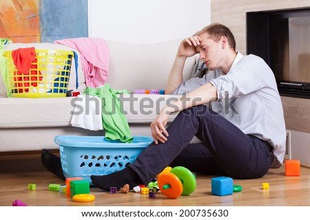 Lonely tired father sitting with child's toys - stock photo