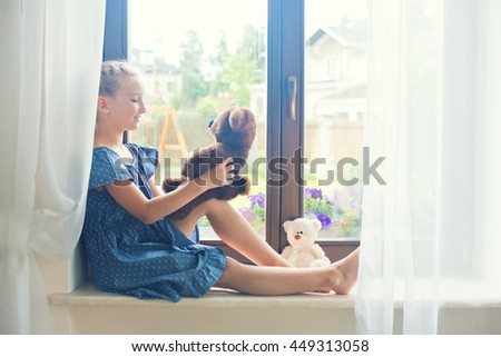 Lonely toddler russian girl sitting near window at home playing teddy bears happy and funny. Colorful back yard at background - stock photo