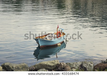 Lonely traditional turkish fishing boat on sea water - stock photo