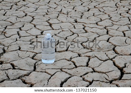 Lonely water bottle on Drought cracked earth