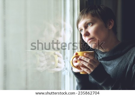 Lonely woman drinking cup of coffee by the window of her living room, looking out with a sad look on her face. Selective focus with shallow depth of field. - stock photo