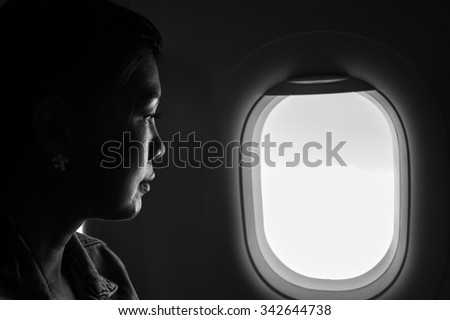 Lonely woman look through plane window. Black and white photo.