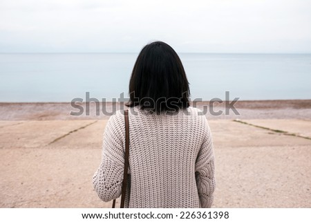 Lonely woman looking at the sea - stock photo
