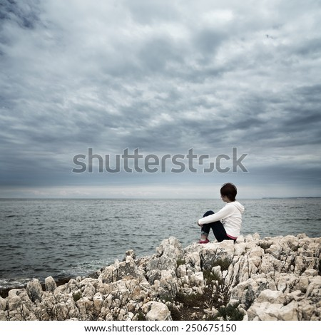 Lonely Woman Sitting at Stormy Sea. Toned and Desaturated Photo with Copy Space. Solitude Concept. - stock photo