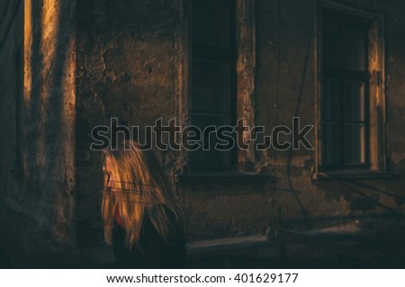 lonely woman sitting in a streak of light surrounded by old building environment