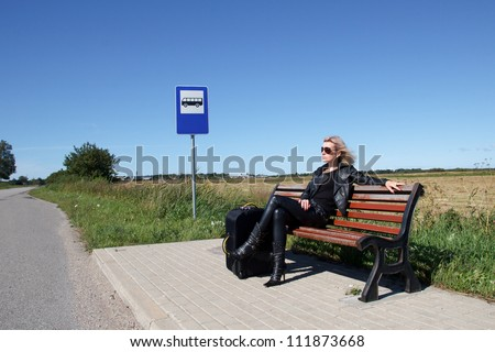 lonely woman sitting on a bench at a bus stop in the countryside - stock photo