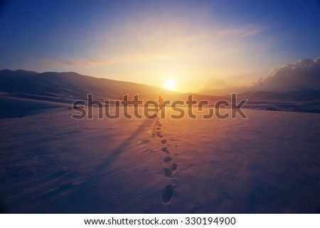 Lonely woman standing far away in bright yellow sunset light, traveling with backpack in the mountains covered with snow - stock photo