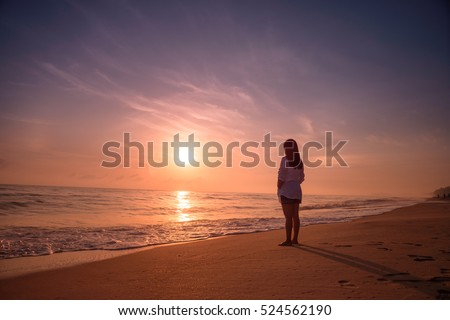 Lonely woman standing on the beach sunset