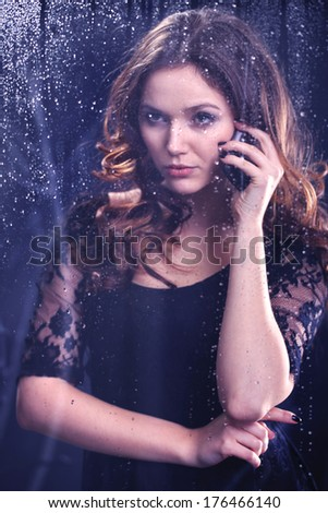 Lonely woman talking on the phone while standing at the window and looks at the night