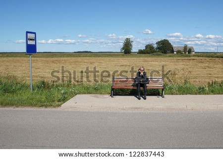 lonely woman waiting for a bus in rural area