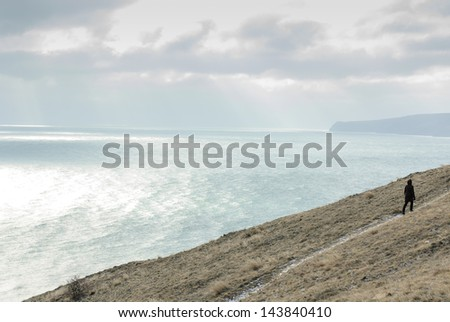 Lonely woman walking along the Black Sea - stock photo