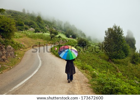 Lonely woman with Colorful Umbrella walking down a winding road between foggy forests in the autumn. - stock photo