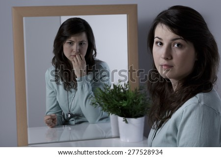 Lonely woman with complexes looking at the mirror