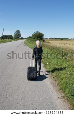 lonely woman with suitcase go along rural roadside