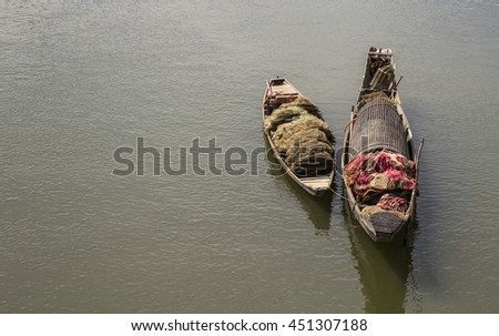 Lonely wooden boats on a river flowing into the sea in Asia - stock photo
