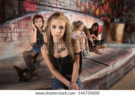 Lonely young female with distracted group near wall - stock photo