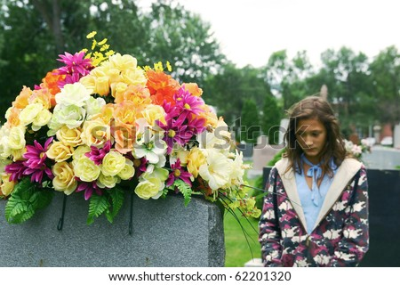 Lonely young girl visiting a grave with colored flowers at the cemetery