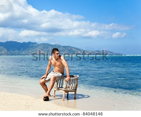 Lonely young man in chair resting on the beach near the ocean