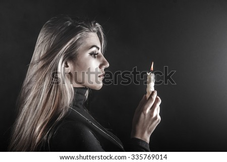 Lonely young woman holding a candle in a smoke - stock photo