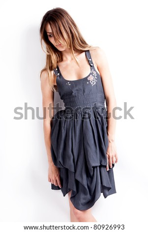 lonely young woman in blue dress, stand, studio shot - stock photo