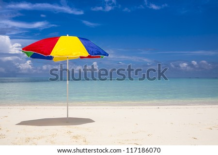 lonesome colorful sunshade at the beach with a blue sky and a turquoise sea