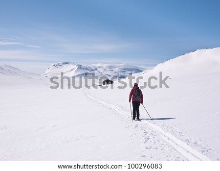 Lonesome female skier approaching a small cottage in norwegian mountains at easter