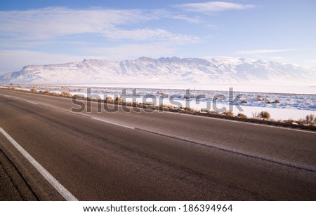 Lonesome Road Winter Freeze Utah Mountain Highway Salt Flats - stock photo