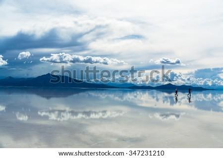 Lonesome Travelers being reflected in Salar de Uyuni, Bolivia - stock photo