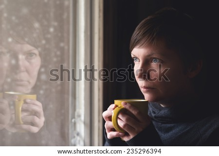 Lonesome woman drinking cup of coffee by the window of her living room, looking out at snow falling with a sad look on her face. Selective focus with shallow depth of field. - stock photo