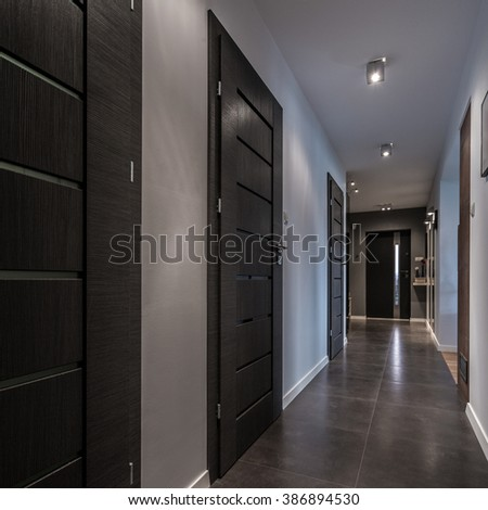 Long and gray corridor in luxury house - stock photo