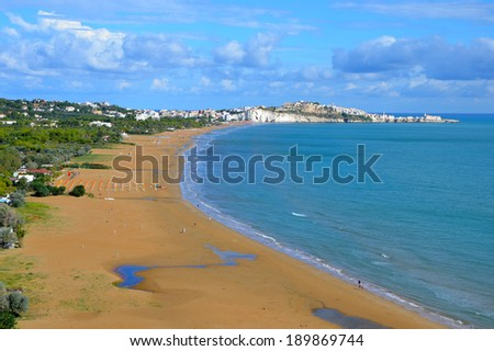 Long and wide beach in Vieste town, Gargano, Italy. Old town of Vieste in the background. - stock photo