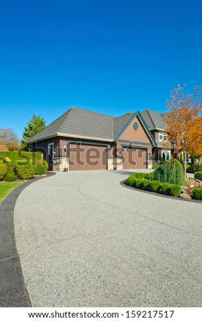 Long and wide nicely paved driveway to two double doors garage in the suburbs of Vancouver, Canada. Vertical.