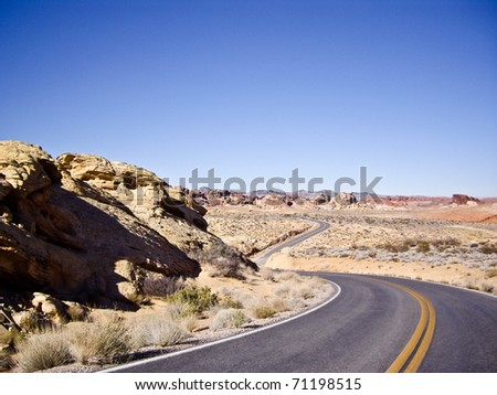 Long and winding desert road curves into the distance