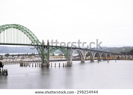 Long arched bridge with sectional arches of different diameters and metal trusses and concrete pillars supporting the bridge connecting two shores of the bay of the Pacific Ocean in Newport Oregon. - stock photo