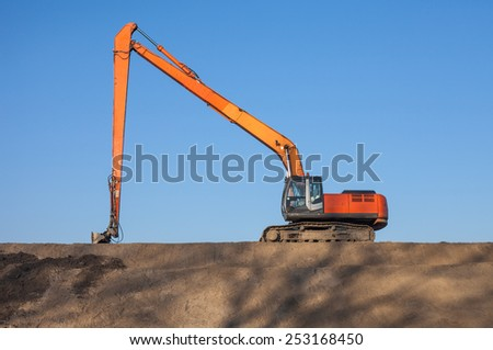 long arm excavator working on sand dunes - stock photo
