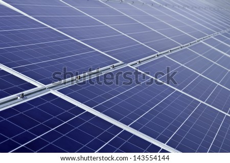 Long array of solar panels in bright sunlight - stock photo