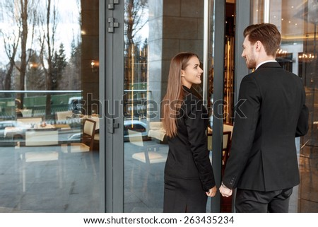 Long-awaited meeting. Businessman and businesswoman smiling to each other open the door of the luxury restaurant - stock photo