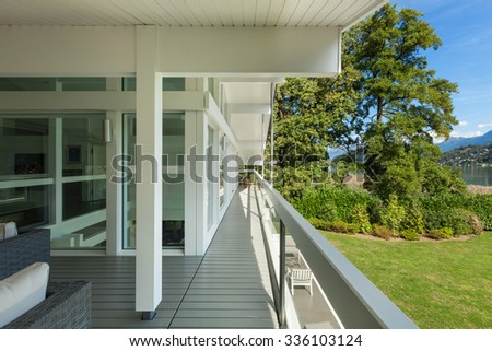 long balcony of a villa on the lake, park view - stock photo